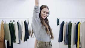 Młoda atrakcyjna kobieta stawia dalej słuchawki, zamyka ona i tanczy w przebieralni, oczy zbiory wideo