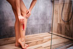 Młoda atrakcyjna seksowna kobieta w prysznic nagie ciało Goli nogi używać ostrą żyletkę _ Well-buil i sporty suchy zdjęcia royalty free