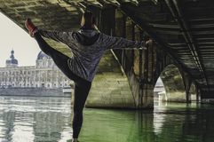 Młoda atrakcyjna sprawności fizycznej kobieta robi ćwiczeniu i rozciąga nogi w mieście Wspaniała architektura w tle obraz stock