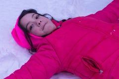 Młoda Azjatycka dziewczyna kłaść w śniegu obrazy stock