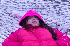 Młoda Azjatycka dziewczyna kłaść w śniegu fotografia royalty free