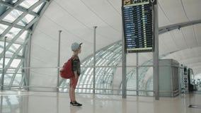 Młoda backpacker sprawdza lota informacja na cyfrowym rozkładu pokazie zbiory