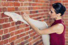Młoda balerina wiąże faborek w ona z nastroszoną nogą buty obrazy royalty free