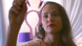 Młoda brunetki kobieta rysuje oświetleniową żarówkę na szklanej ścianie Biznes, edukacja i ludzie pojęć, 3840x2160 zbiory wideo