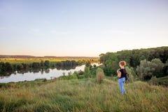 Młoda dziewczyna kontempluje piękno natura Dziewczyna od wzgórzy spojrzeń przy rzeką i forest_ zdjęcia stock