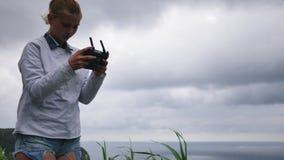 Młoda dziewczyna kontroluje trutnia w wietrznej pogodzie przeciw tłu potężny ocean zbiory