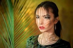 Młoda dziewczyna portret z cieniami z od palma liści ubierał w górę cosplay kobiety w dżungli jako zdjęcia stock