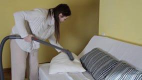 Młoda dziewczyna używa próżnię czystą czyścić pył w poduszce zbiory wideo