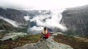 Młoda dziewczyna z długie włosy w czerwonej bluzie sportowej chodzi w górach Norwegia fjords zbiory