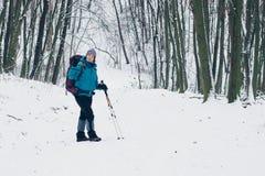 Młoda dziewczyna z plecakiem obraca wokoło zostawać na ścieżce w zima lesie zdjęcie stock