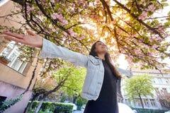Młoda dziewczyna z rękami szeroko otwarty i enjoing czereśniowego drzewa ulicę fotografia stock