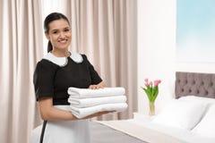 Młoda gosposi mienia sterta świezi ręczniki w pokoju hotelowym obraz royalty free