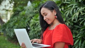 Młoda Indonezyjska dziewczyna z laptopem w ręce w parku zbiory wideo