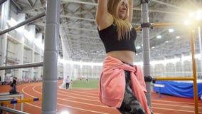 Młoda kobieta ciągnie w górę crossbar w sport sali na Pompować niskie części jej ciało zbiory