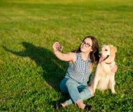 Młoda kobieta i jej życzliwy pies bierze selfie przy parkiem fotografia stock