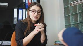 Młoda kobieta która pracuje gdy księgowy w firmie prawniczej egzamininuje dokumenty za jej miejsce pracy Młoda kobieta otrzymywa zbiory