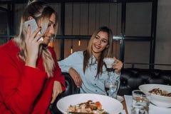 Młoda kobieta opowiada na telefonie podczas lunchu z jej przyjacielem obraz royalty free
