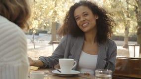 Młoda kobieta opowiada przyjaciel podczas gdy siedzący z kawą w outdoors restauracji zbiory