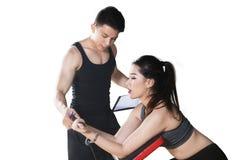 Młoda kobieta pomagać trenerem ćwiczyć zdjęcia stock