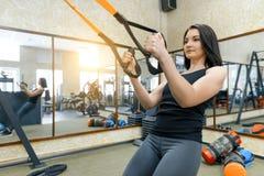 Młoda kobieta przy gym robi sprawności fizycznych ćwiczeniom używa sporty troczy system, trzyma ręki pętlami sprawność fizyczna,  fotografia stock