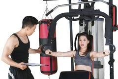 Młoda kobieta robi treningowi z jej trenerem obrazy royalty free
