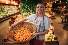 Młoda kobieta stojak przy owoc pudełkami w sklepie spożywczym Trzyma kosz z pomarańczami i pozuje na kamerze Jest ubranym fartuch obrazy stock