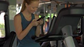 Młoda kobieta trzyma telefon przed ona przy gym na ćwiczenie rowerze oczy w jej rękach Wszystkie uwaga jest zbiory wideo