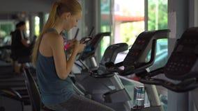 Młoda kobieta trzyma telefon przed ona przy gym na ćwiczenie rowerze oczy w jej rękach Wszystkie uwaga jest zdjęcie wideo