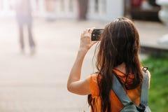 Młoda kobieta turysta z plecakiem bierze obrazki na smartphone outdoors zdjęcia stock