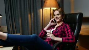 Młoda kobieta w biurze ma przerwę Opowiadający telefon komórkowego i napoje kawowych zdjęcie wideo