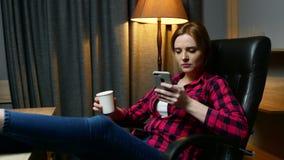Młoda kobieta w biurze ma przerwę Pisać na maszynie wiadomość na telefonie komórkowym i pić kawę zbiory