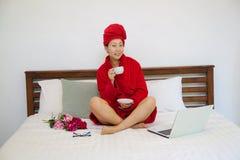 Młoda kobieta w czerwonym bathrobe na łóżku z laptopem i filiżanką obraz stock