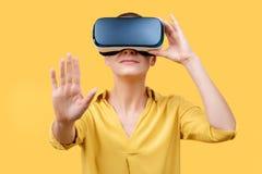 Młoda kobieta w jej 30s używać rzeczywistość wirtualna gogle Kobieta jest ubranym VR szkła odizolowywających nad żółtym tłem Vr d zdjęcie stock