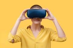 Młoda kobieta w jej 30s używać rzeczywistość wirtualna gogle Kobieta jest ubranym VR szkła odizolowywających nad żółtym tłem Vr d obrazy stock