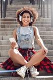 Młoda kobieta w miasta ulicznym obsiadaniu na schodkach z cent deską słucha muzycznego mienia smartphone w hełmofonach obraz stock