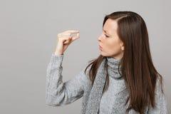 Młoda kobieta w szarym pulowerze, szalika mienie, patrzeje na lekarstwo pastylce, aspiryny pigułka w ręce odizolowywającej na pop obraz royalty free