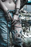 Młoda kobieta w upiększonych niebiescy dżinsy boho stylu rękach z bransoletek i pierścionków lata modą obraz royalty free