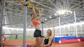 Młoda kobieta z blondynka włosy ciągnie w górę crossbar w sport sali z trenera pomagać na zdjęcie wideo