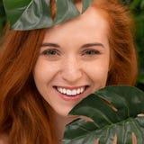 Młoda kobieta z doskonalić uśmiechem z tropikalnymi liść zdjęcia stock