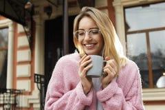Młoda kobieta z filiżanką gorący napój zdjęcia stock