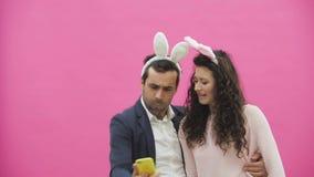Młoda kochanek para na różowym tle Z osłuchanymi ucho na głowie Podczas to dziewczyna jest ubranym królików ucho zbiory wideo