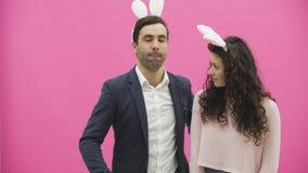 Młoda kochanek para na różowym tle Z osłuchanymi ucho na głowie Podczas to fotografie Sephi na zbiory wideo