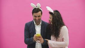 Młoda kochanek para na różowym tle Z ravenous ucho na głowie Podczas ten Wielkanocnej fotografii, sephi robi na telefonie zbiory wideo