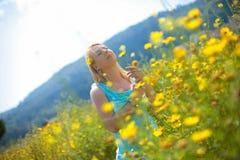 Młoda piękna blondynki dziewczyna w chamomile polu stoi pozować z kwiatem w ona ręki zdjęcie stock