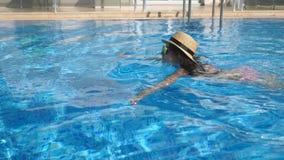 Młoda piękna dziewczyna w okularach przeciwsłonecznych i kapeluszowym dopłynięciu w basenie Kobieta relaksuje w jasnym grże wodę  zdjęcie wideo