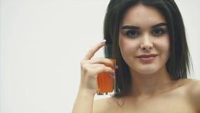Młoda piękna kobieta jest ubranym białego majeka trzyma sok pomarańczowego w jej ręce Portret odizolowywający na Białym tle zdjęcie wideo