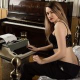 Młoda piękna kobieta pisać na maszynie na retro maszynie do pisania żeński pisarz w staniku i mężczyźni spodniowi obraz royalty free