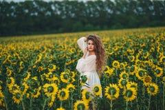 Młoda piękna kobieta w sukni wśród kwitnących słoneczników Kultura zdjęcia stock