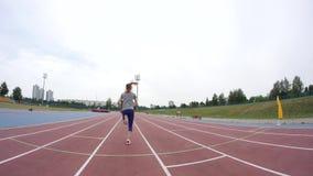 Młoda piękna sport kobieta zaczyna biegać przy miasto atletyki śladem podczas dnia szkolenia w zwolnionego tempa 4K wideo zbiory