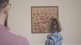 Młoda rodzina ruszająca się nowy mieszkanie Pojęcie chodzenie nowy dom Mąż zadawalający jako żona wieszał obrazek zbiory wideo